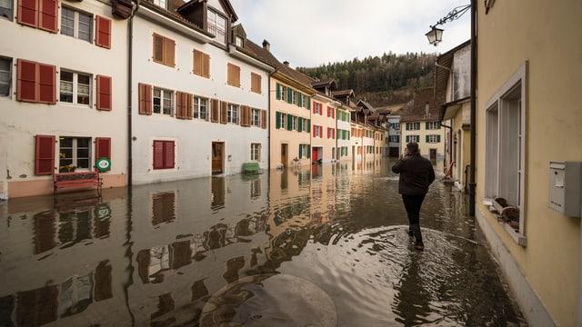 Mann watet durch das Wasser. Regenfälle haben die Strassen überschwemmt.
