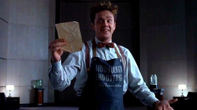 Ein Mann in Schürze hält ein Blatt Papier mit einem Kreis in die Höhe.