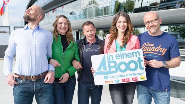 Gruppenfoto vor dem Schiff mit den drei Moderatoren und den beiden Moderatorinnen.