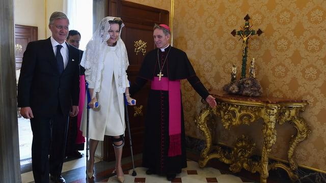 König Philippe und Königin Mathilde laufen durch Tür.