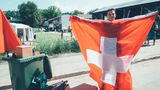 Mann hisst Schweizer Flagge und hat grüne Tonne dabei.