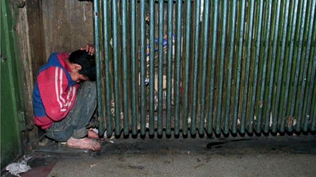 Ein Knabe mit nackten, schmutzigen Füssen kauert in einem Bahnhof in einer Ecke und presst sich an einen Heizkörper bei Minustemperaturen.