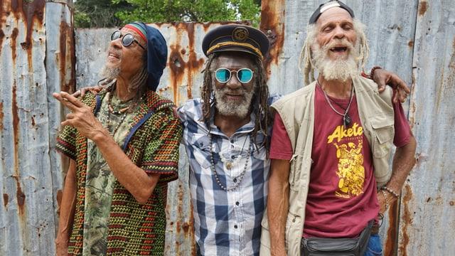 Drei Reggae-Musiker vor einem zaun.