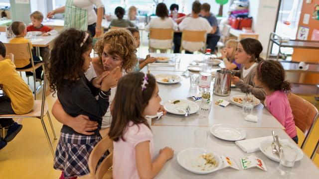 Mittagstisch in einer Kinderkrippe. Die Betreuerin spricht intensiv mit einem Mädchen.