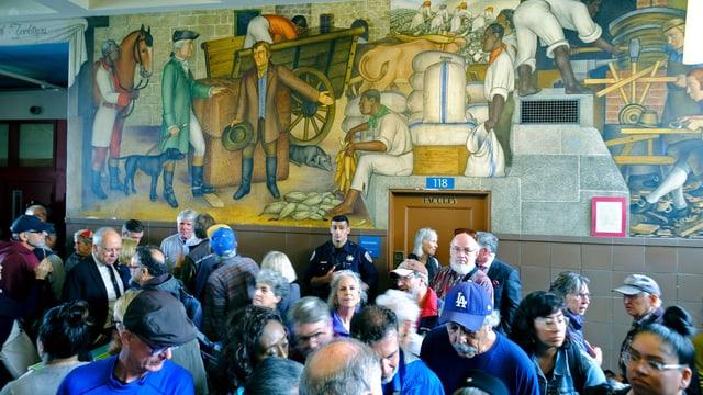 Viele Leute stehen in einer Halle in der Schule, hinter ihnen ist eine bemalte Wand.