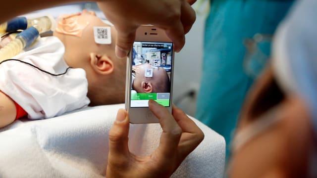 Eine Person mit OP-Kleidung macht ein Handyfoto eines Säuglings mit Atemschläuchen in einem Spital.