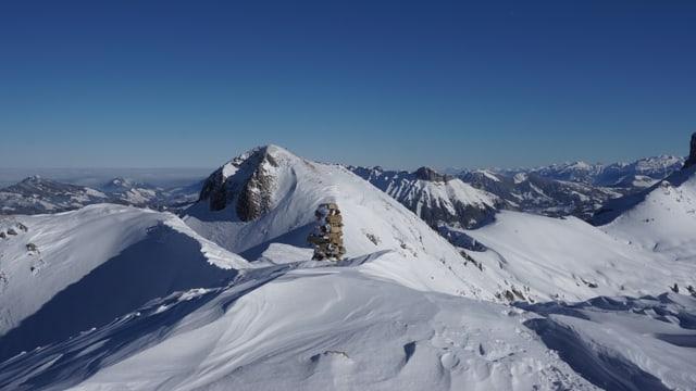 Blick über die schneebedeckten Berge des Berner Oberlandes bei wolkenlosem Himmel.