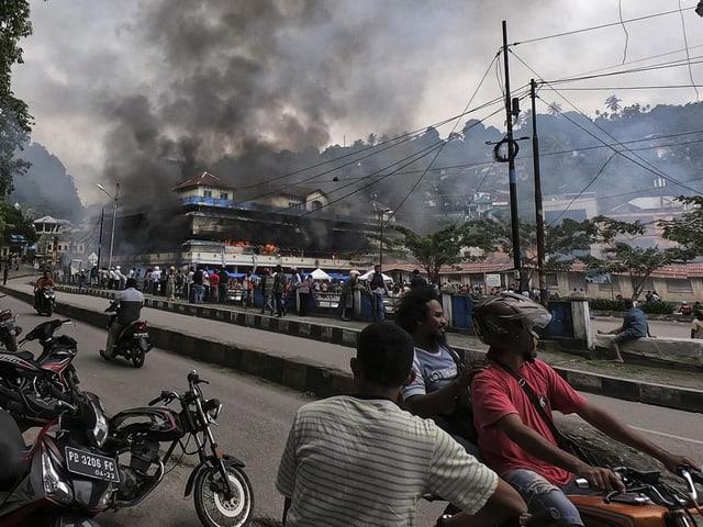 Demonstranten in West Papua und ein brennendes Haus