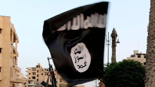 Ein IS-Aktivist schwenkt eine schwarze Flagge der Dschihadisten.