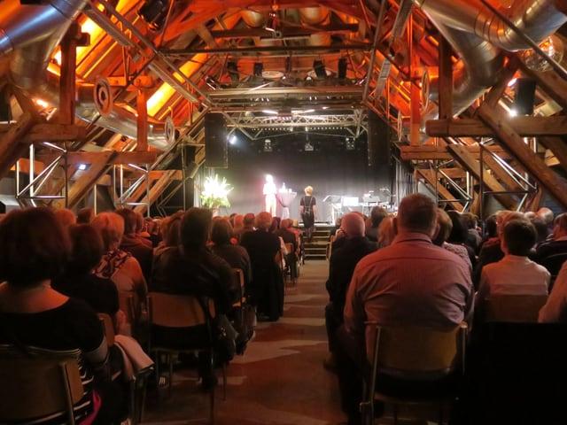 Voller Saal mit vielen Menschen und einer Bühne