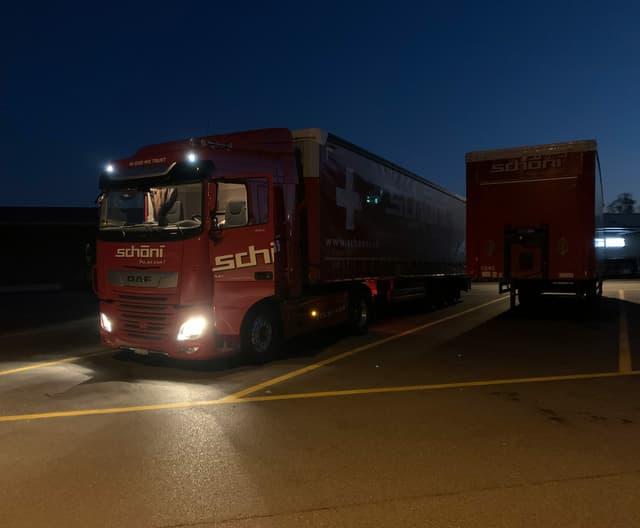 Lastwagen auf einem Parkplatz im Morgengrauen.