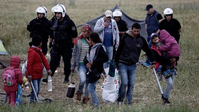 Griechische Polizisten beobachten syrische Flüchtlinge, die das Camp in Idomeni verlassen.