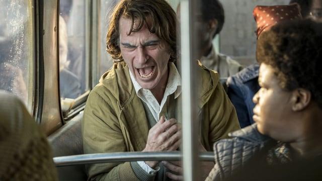 Ein älterer Mann sitzt in einer U-Bahn und lacht krampfhaft.