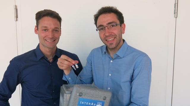 Zwei Personen stehen im Bild. Martin Ostermaier steht rechts und zeigt sein neues Produkt.