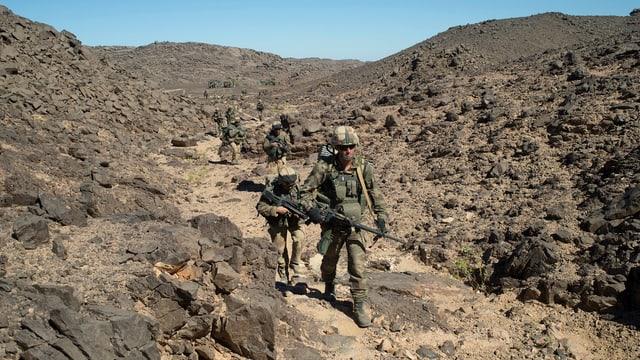 Französische Soldaten in Uniform auf unwegsamem Gelände