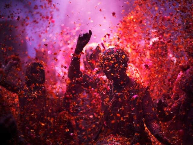 Farbige Menschen tanzen, in der Luft fliegen Blütenblätter.