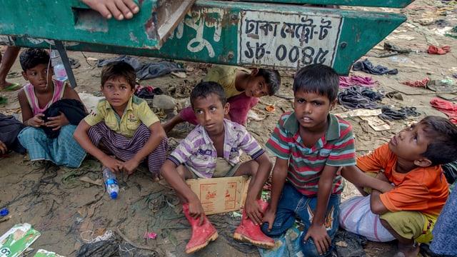 Rohingya-Kinder sitzen in einem Flüchtlingslager in Bangladesh unter einem Transporter für Hilfsgüter.