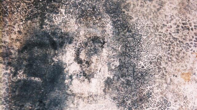 Undeutliche dunkle Flecken auf der Wand, die entfernt an ein Gesicht erinnern.