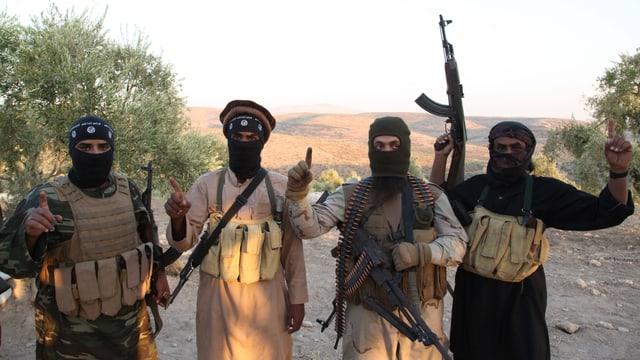 Vier vermummte, schwer bewaffnete Kämpfer posieren in ländlichem Gebiet.