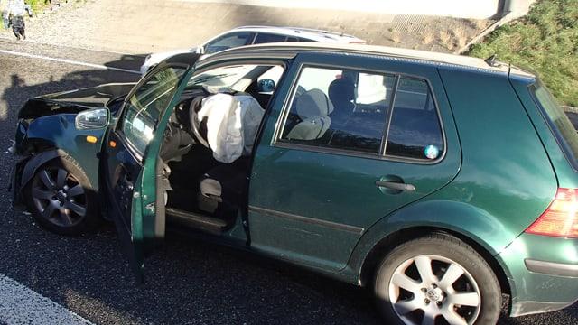 Ein grünes Unfallauto mit zerdrücktem Kotflügel.