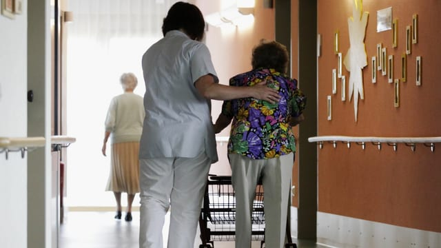 Das Bild zeigt eine Pflegefachperson, die eine ältere Frau stützt.