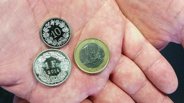 Hand hält Geldstücke: 1 Euro, 1 Franken und ein 10-Räppler.