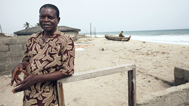 Agbakla steht vor den Ruinen seines Hauses. Im Hintergrund der Strand und das Meer.