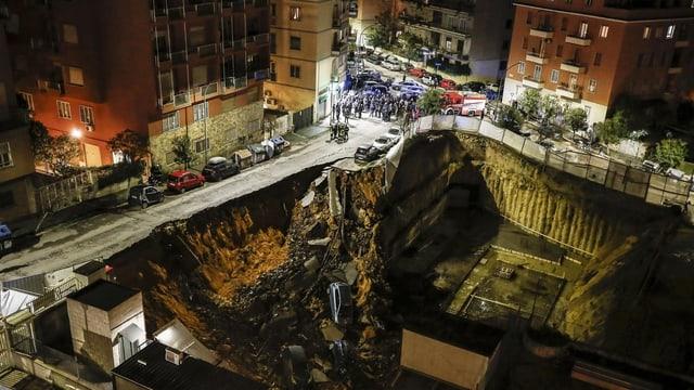 Nachtszene: Inmitten von Häuserzeilen öffnet sich ein riesiges Loch, in dem Autos liegen.