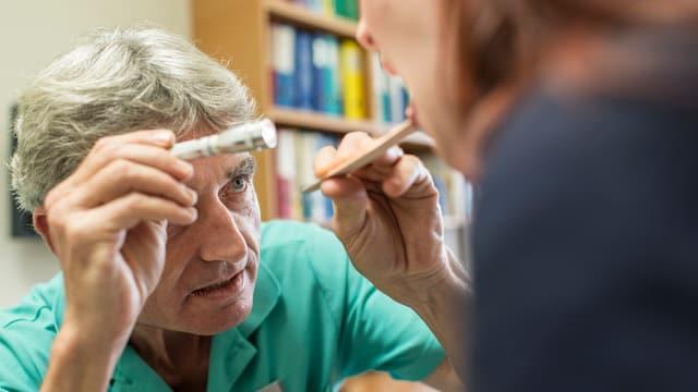 Arzt leuchtet einer Patientin in den Mund.