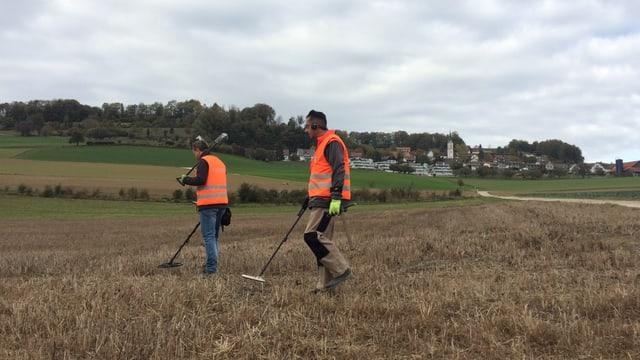 Zwei Männer stehen mit technischen Geräten auf einem Feld.