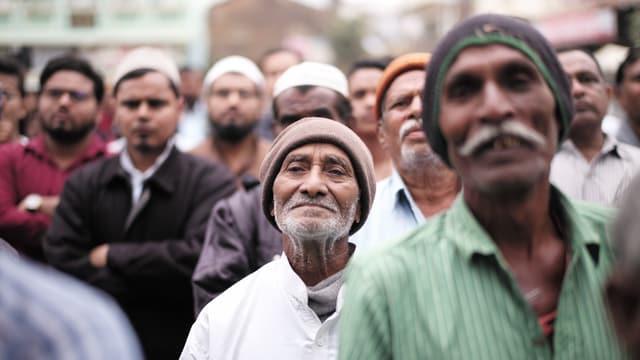 Bewohner des Dorfes Wadgam stehen vor eine Rednertribüne.