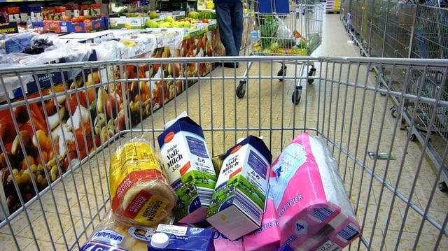 Ein halb gefüllter Einkaufswagen wird in einem Supermarkt herumgeschoben.
