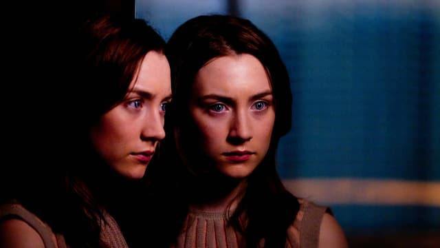 Die Hauptdarstellerin steht nachdenklich blickend neben einem Spiegel, der sie doppelt erscheinen lässt.