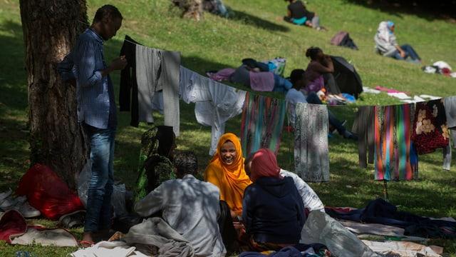 Fugitivs en in parc datiers da la staziun da Como.