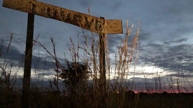 Ein rostiges Schild auf einer Wiese in der Morgendämmerung.