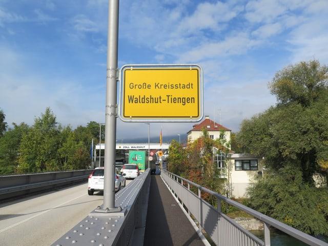 Ortsschild Waldshut an Brückengeländer, Autos fahren über Brücke, Bäume.