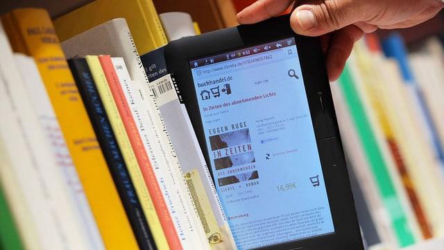 Aus einem Gestell mit herkömmlichen Büchern wird ein E-Reader mit Eugen Ruges «In Zeiten des abnehmenden Lichts» herausgezogen.