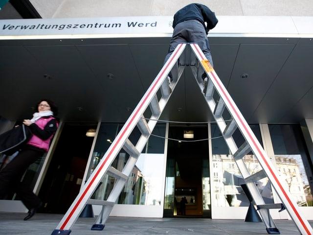 Mann auf einer Leiter vor dem Eingang zum städtischen Verwaltungszentrum Werd.