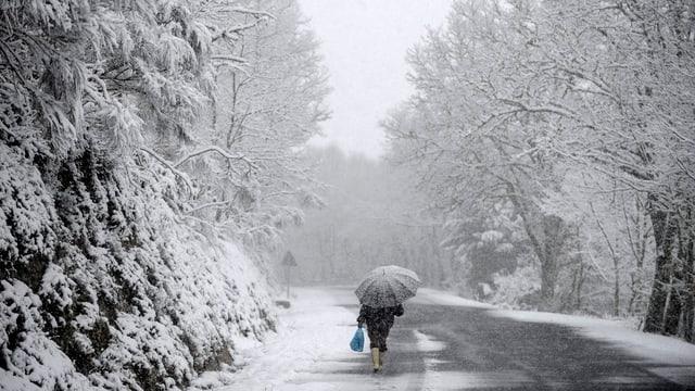 Spaziergänger mit Regenschirm an einer verschneiten Strasse.