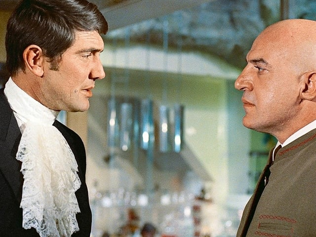 Bonddarsteller mit weissem Schal und glatzköpfiger Mann in militärischer Uniform.