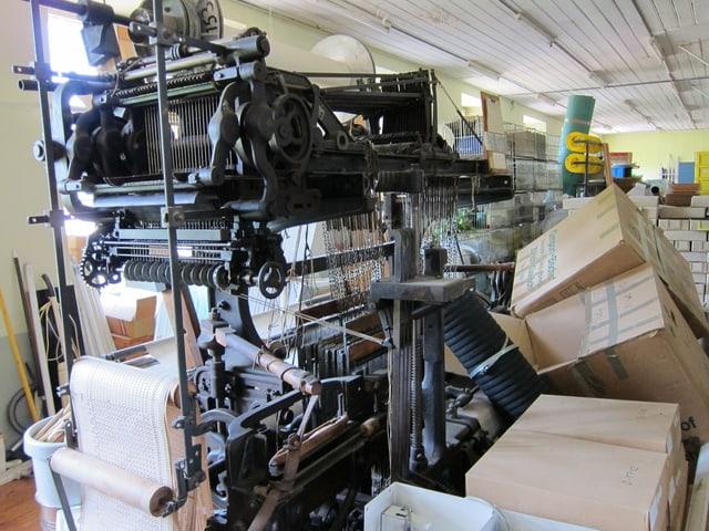 Webstuhl zwischen verschiedenen Kisten in der Fabrik