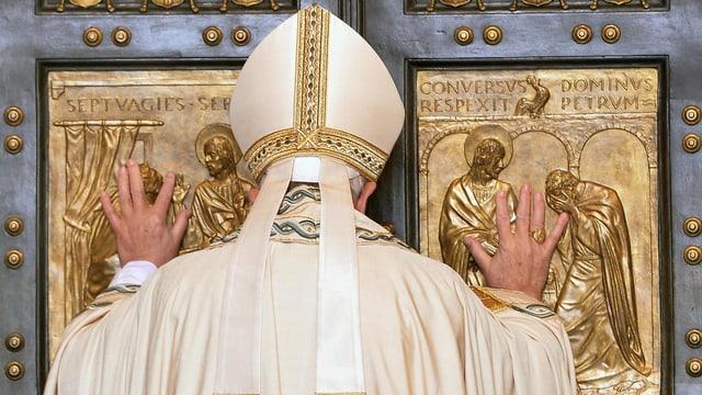 Papst Franziskus von hinten fotografiert drückt mit beiden Händen gegen die heilige Pforte der St. Peters Basilika in Rom