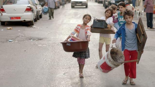 Vier Kinder tragen Baumaterial durch eine Strasse.