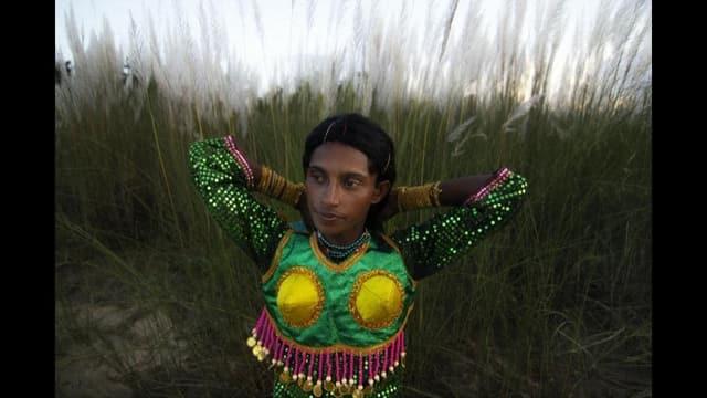 Ein junger Mann in bunt glitzerndem Kleid vor einer Wiese