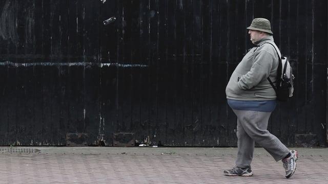 Ein übergewichtiger Mann läuft auf einem Gehsteig entlang.