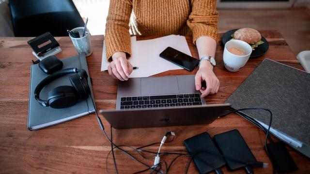 Person im Homeoffice mit mehreren Computern auf dem Tsich.
