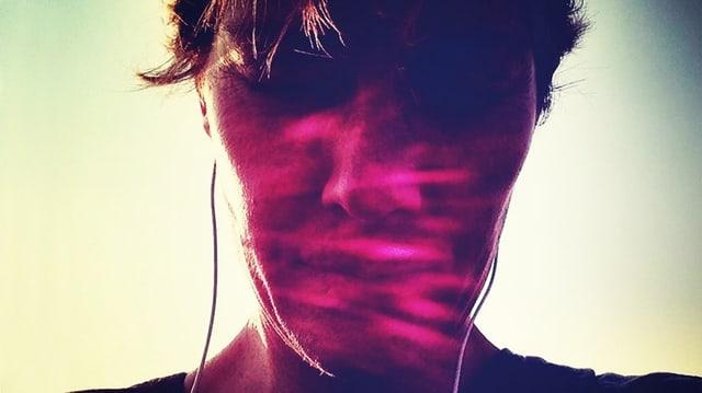 Das Gesicht eines Menschen mit geschlossenen Augen, leichtem Lächeln und Kopfhörern. Die Aufnahme ist im Gegenlicht gemacht, sodass rosafarbene Strahlen auf dem Gesicht erscheinen.
