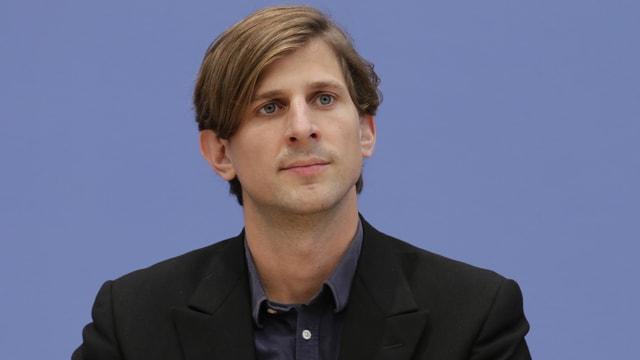 Junger Mann mit Seitenscheitel vor blauem Hintergrund.