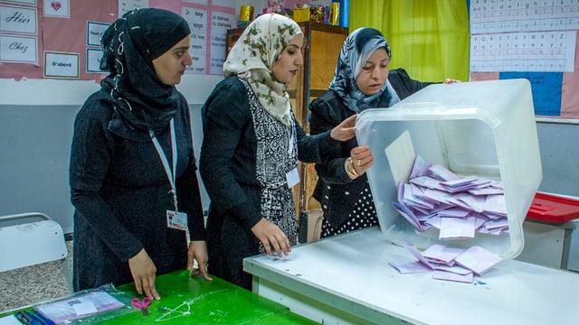 Drei Frauen mit Kopftuch leeren eine Wahlurne aus Plastik.