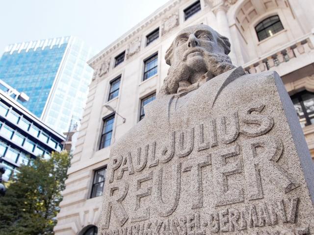 Eine Statue von Paul Julius Reuter steht im Vordergrund, dahinter sieht man Hochhäuser.